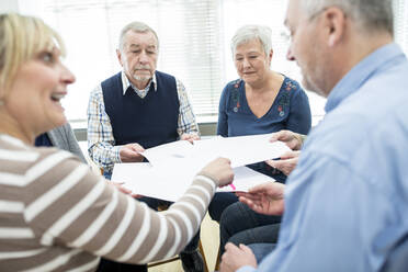 Group of seniors attending therapy group in retirement home, using sheets of paper - WESTF24609