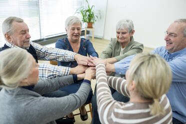 Group of active seniors stacking hands, symbolizing solidarity - WESTF24612
