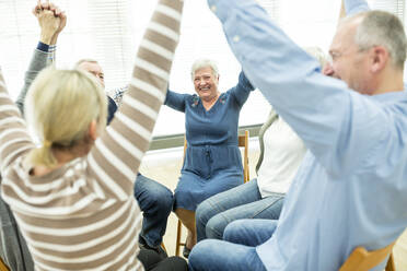 Group of seniors practicing chair gymnastics with instructor  in retirement home - WESTF24624