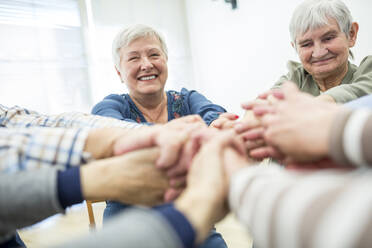Group of active seniors stacking hands, symbolizing solidarity - WESTF24627