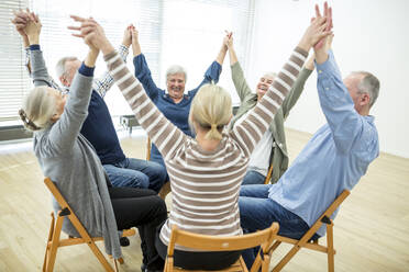 Group of seniors practicing chair gymnastics with instructor  in retirement home - WESTF24630