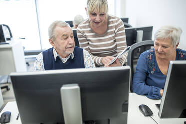 Active seniors attending computer course, intructor giving advice - WESTF24651