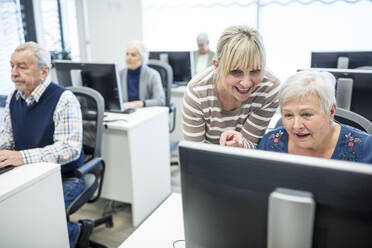 Active seniors attending computer course, intructor giving advice - WESTF24654