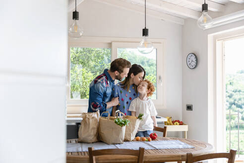 Smiling man looking at woman kissing son while standing at dining table with groceries in kitchen - EIF00019
