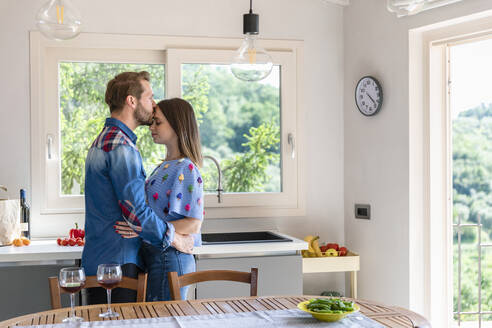 Man kissing woman while standing by dining table in kitchen at home - EIF00031