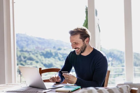 Smiling handsome man holding credit card while using laptop at dining table against window - EIF00055