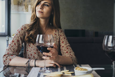 Beautiful young woman holding wineglass looking away while sitting at dining table - SBAF00013