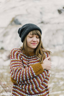 Attractive young lady in sweater and hat with crossed hands near hill on blurred background in Pyrenees - ADSF00661