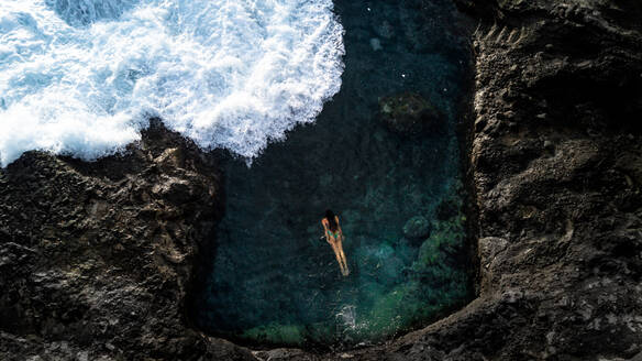 Aerial view of relaxed female swimming in beautiful water of lagoon with cliffs around and waves with white sea foam rolling up shore - ADSF00778