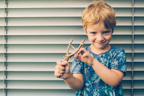 Blonde boy playing with a slingshot - ADSF00934