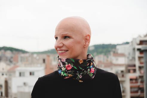 Bald woman standing on rooftop with city behind - ADSF00955