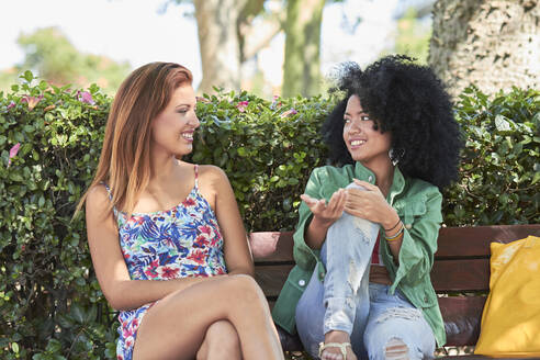 Girlfriends talking and sitting on bench - PGCF00082