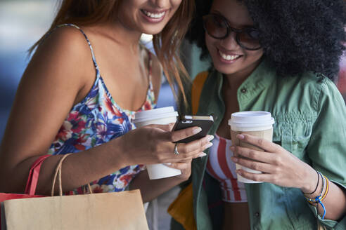 Girlfriends with coffee to go using smartphone - PGCF00094