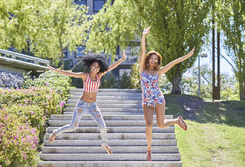 Girlfriends jumping from stairs in park - PGCF00100