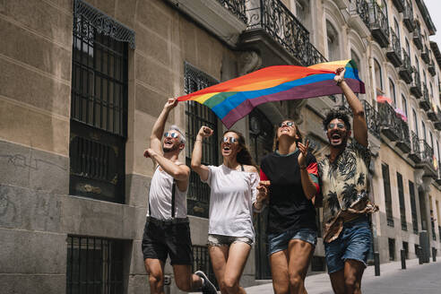 Group of friends with a flag of gay pride in the city of Madrid - ADSF00984