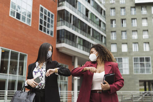 Young multi-ethnic female colleagues giving elbow bump against building in city - MTBF00539