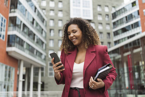 Smiling young businesswoman using smart phone while standing against building in city - MTBF00542