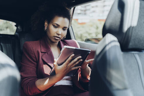 Young female entrepreneur using digital tablet while sitting in car - MTBF00557