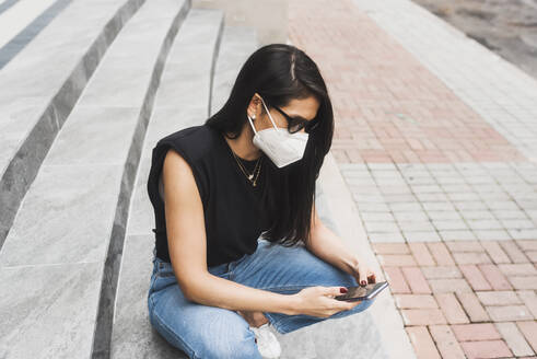 Woman with protective mask using smartphone on steps in city - DSIF00022