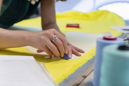 Female fashion designer marking on yellow fabric at studio - EIF00088