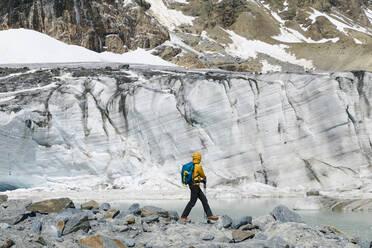 Male hiker exploring melting glacier while standing on rocks - MCVF00505