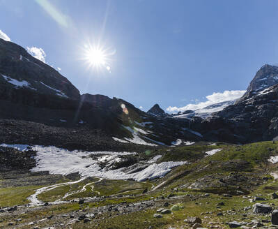 Scenic view of mountain range with melting glacier streams against sky on sunny day - MCVF00514