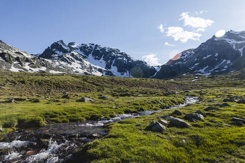 Stream flowing from melting snow near mountains against sky on sunny day - MCVF00517