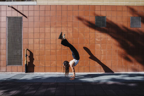 Young woman performing handstand on sidewalk against tiled wall in city - MEUF01304