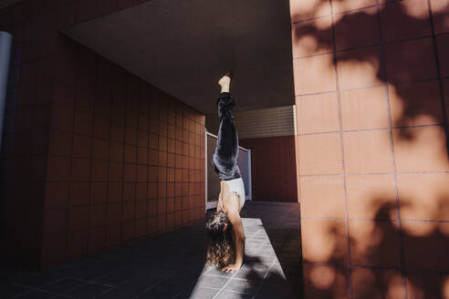 Young woman performing handstand in tunnel during sunny day - MEUF01310