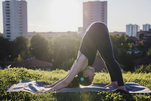 Young woman performing yoga in downward facing dog position at city park - MEUF01325