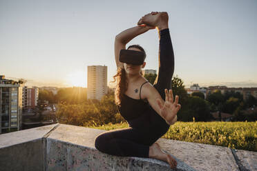 Flexible young woman using VR glasses while performing yoga on retaining wall in city during sunset - MEUF01331