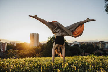 Young woman performing handstand at city park during sunset - MEUF01349