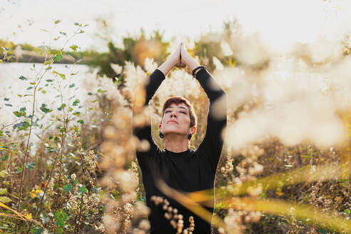 Woman with eyes closed and arms raised exercising while standing amidst plants - MRRF00122
