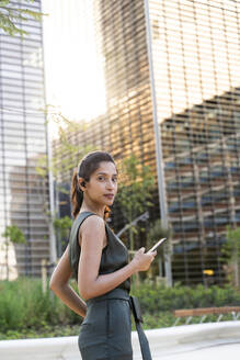 Confident businesswoman using mobile phone while standing against modern buildings in city - AFVF06731