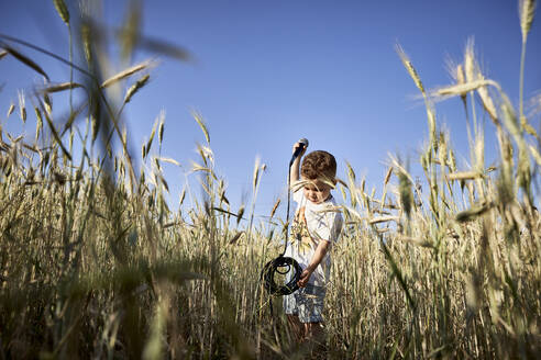 Boy holding microphone while standing amidst crops against clear blue sky - VEGF02525