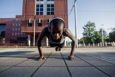 Female athlete with shaved head listening music through headphones while doing push-ups on street in city - MEUF01407