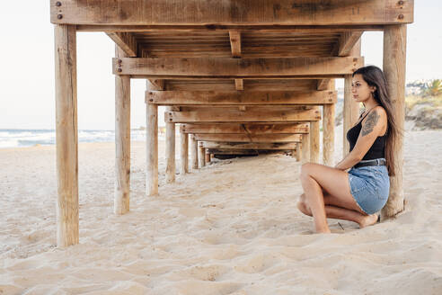 Thoughtful teenage girl sitting under pier at beach - DLTSF00874