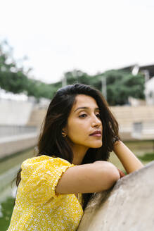 Thoughtful woman leaning on retaining wall in city - AFVF06797