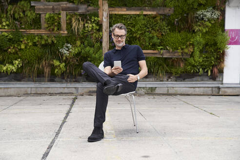 Mature man using smart phone while sitting on chair at yard - SUF00634