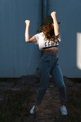 Female hip-hop dancer dancing against wall during sunny day - JMPF00175