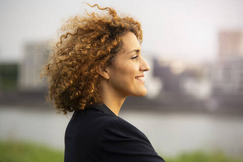 Close-up of smiling businesswoman with curly hair looking away in city - MJFKF00510