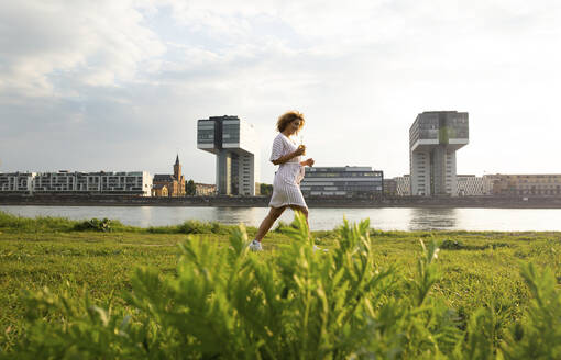 Woman with beer bottle walking on grassy land against river in city at sunset - MJFKF00516