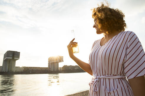 Smiling woman with curly hair holding beer bottle while looking at river in city during sunset - MJFKF00522