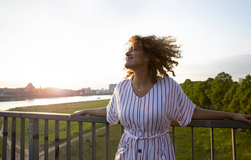 Smiling mid adult woman with curly hair standing by railing against sky at sunset - MJFKF00528