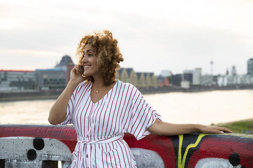 Cheerful woman with curly hair talking over smart phone while standing by railing against sky during sunset - MJFKF00537