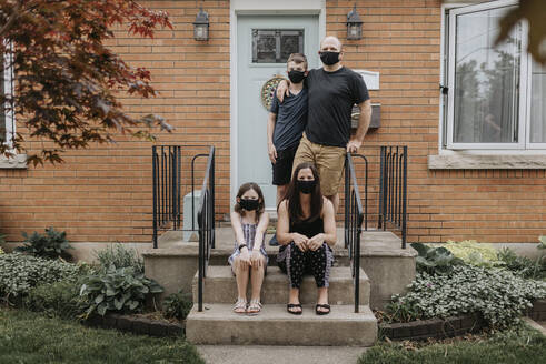 Family wearing masks against house in yard - SMSF00037