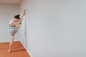 Girl stretching legs by white wall at home - SMSF00052