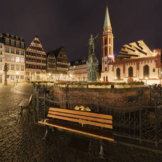 Empty bench on Romerberg in Frankfurt, Germany at night, during the Corona virus crisis. - CUF55950