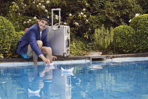Smiling man floating paper boats on swimming pool while sitting by suitcase against plants - UKOF00006