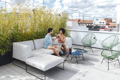 Multi-ethnic couple toasting red wine glasses while sitting on sofa at penthouse terrace - EHF00556